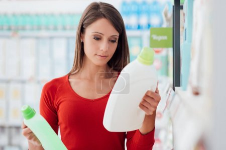 Photo for Woman shopping at the supermarket and comparing detergent products, she is reading labels - Royalty Free Image