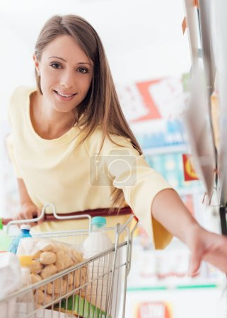 Woman taking products from shelf