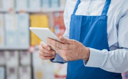 Supermarket clerk using apps on tablet