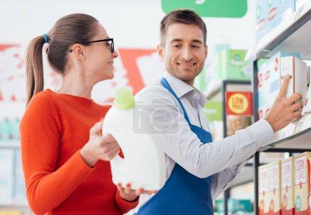 Supermarket clerk helping customer