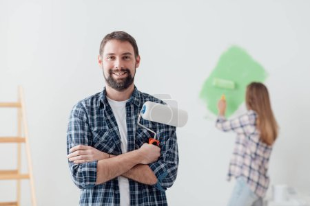 man posing with paint roller