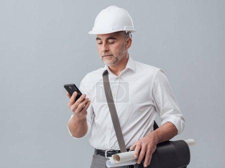 Construction engineer using  smartphone