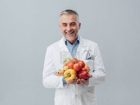 Smiling nutritionist holding vegetables