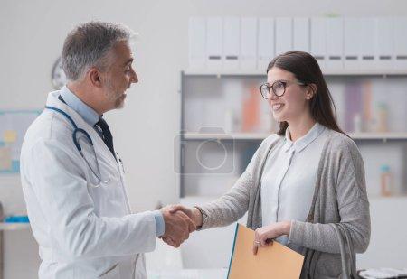 Photo pour Souriant médecin confiant serrant la main d'une patiente dans le bureau, elle détient des dossiers médicaux - image libre de droit