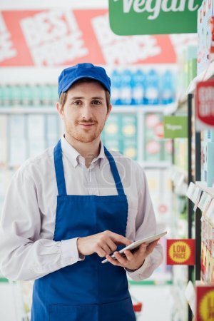 Professional supermarket clerk using  tablet