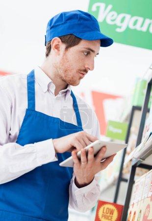 supermarket clerk working with digital tablet