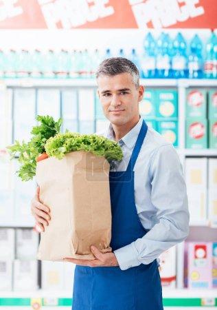supermarket clerk holding grocery bag