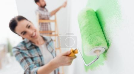 Happy couple painting walls in new house
