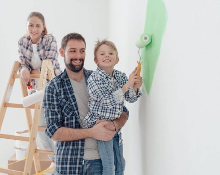 father holding son with paint roller