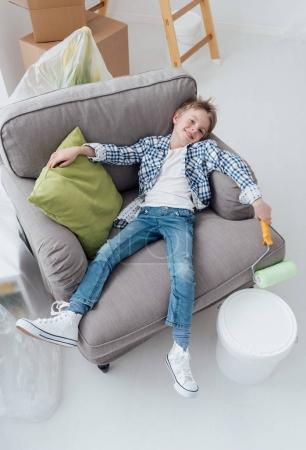 boy liying on armchair with paint roller
