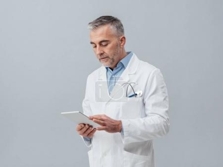 Confident doctor using  digital tablet