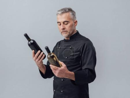 Professional chef comparing wine bottles