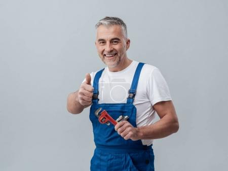 Photo for Cheerful repairman giving thumbs up while smiling and holding adjustable wrench - Royalty Free Image