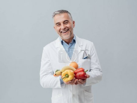 Smiling nutritionist holding vegetables and fruit