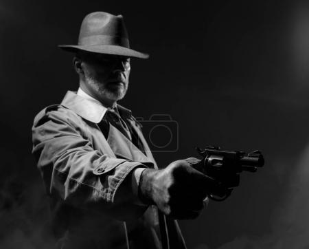 Spy agent pointing gun in dark