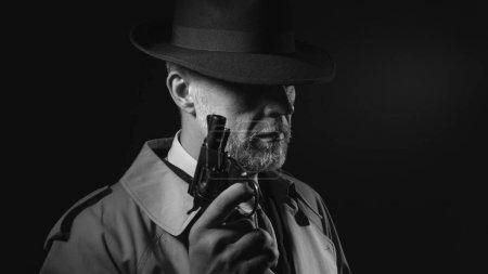 Detektiv hält Waffe im Dunkeln