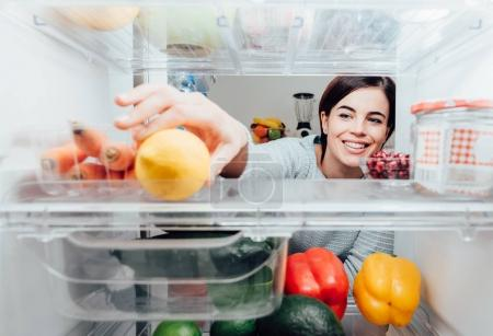 Woman taking lemon out of fridge