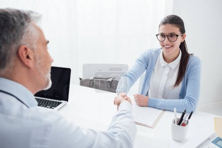 examiner shaking hand of smart woman