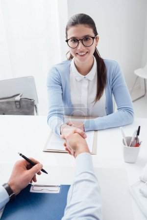 examiner shaking hand of smart woman