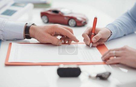 Foto de Agent helping at woman signing car insurance policy - Imagen libre de derechos