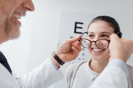 ophthalmologist putting glasses on woman