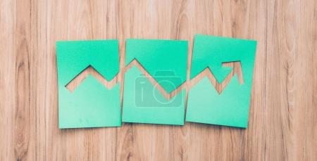 Photo pour Graphique financier réussi avec flèche pointant vers le haut composé de coupes de papier vert, bureau en bois sur le fond - image libre de droit