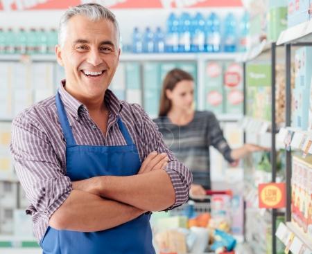 Confident supermarket clerk at shopping mall