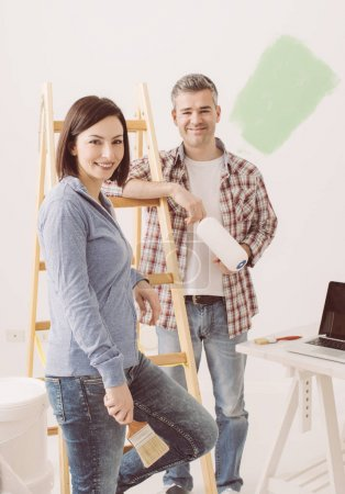 Smiling couple painting house