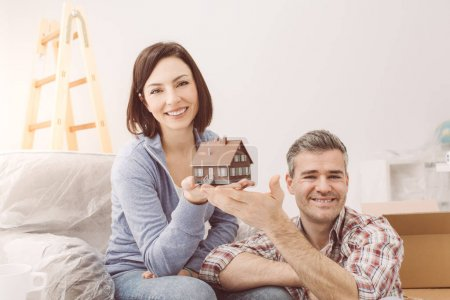 smiling couple holding model house