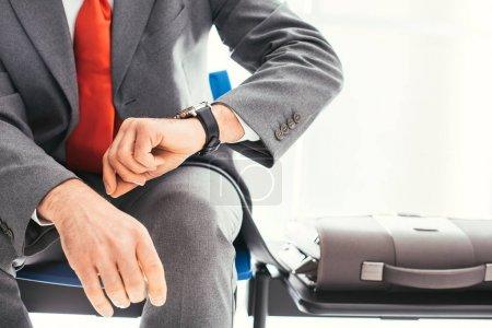 Photo pour Homme d'affaires d'entreprise assis dans la salle d'attente et vérifiant l'heure, il attend la réunion - image libre de droit
