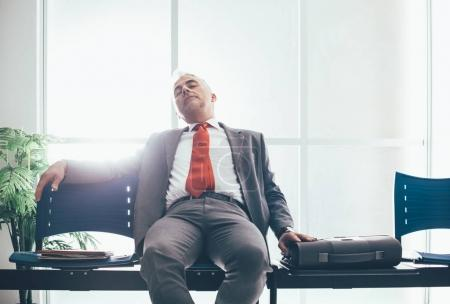 Tired businessman sleeping in waiting room