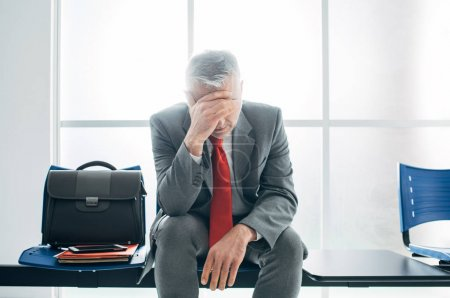 Photo for Depressed stressed businessman sitting in the waiting room and waiting for a job interview, unemployment and business failure concept - Royalty Free Image