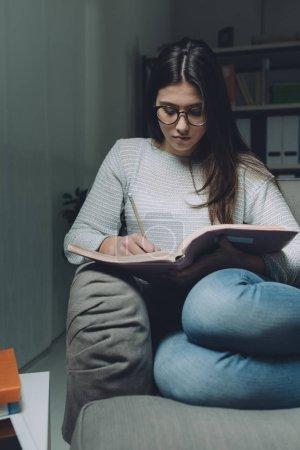 Photo pour Fille étudiant la veille de l'examen, elle lit un livre et écrit des notes avec un crayon - image libre de droit