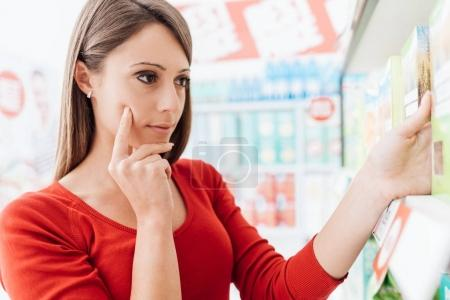 woman choosing products on supermarket shelves