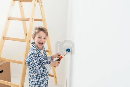 Happy cute boy painting wall
