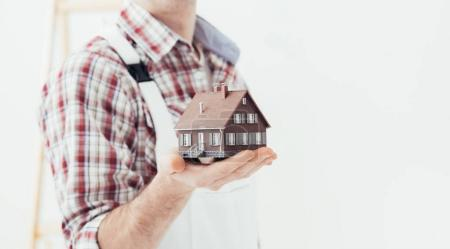 Building contractor holding model house