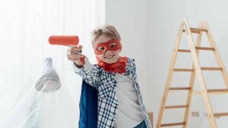 superhero boy holding paint roller