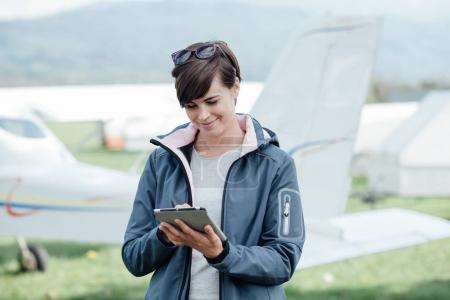 Female pilot with digital tablet
