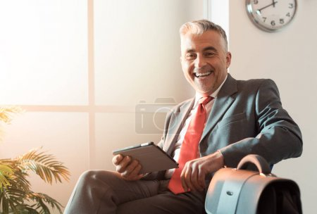 Businessman in waiting room with tablet
