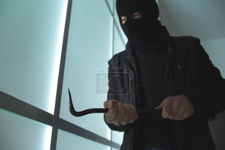 Dangerous burglar using crowbar