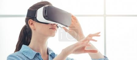 Photo for Young woman experiencing virtual reality, she is wearing a VR headset and interacting with a virtual environment, innovative technology concept - Royalty Free Image