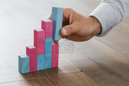 Businessman building growing financial graph