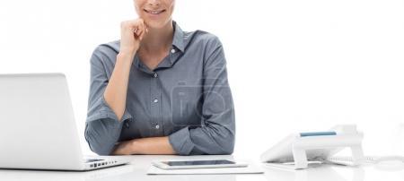 Photo pour Femme d'affaires jeune professionnel travaillant au bureau avec son ordinateur portable et souriant à la caméra - image libre de droit