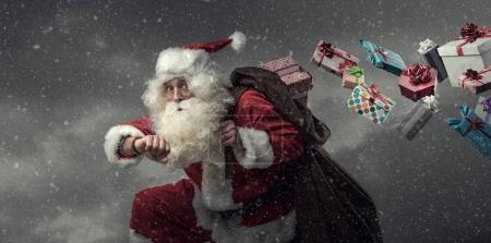 Photo for Santa Claus running and delivering presents on Christmas Eve: he is late and losing gifts from his sack - Royalty Free Image
