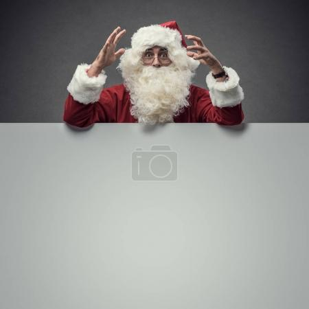 Photo for Surprised happy Santa Claus with big blank sign, Christmas and celebrations concept - Royalty Free Image