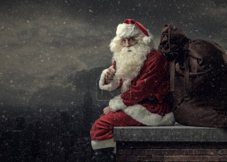 Photo for Happy Santa Claus bringing gifts on Christmas Eve: he is sitting on a roof, carrying a big sack and giving a thumbs up - Royalty Free Image