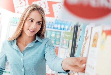 Attractive happy woman at the supermarket, she is doing grocery shopping and taking products on the shelf