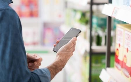 Man shopping at the supermarket, he is searching products on the shelf and using apps on his smartphone, retail and technology concept