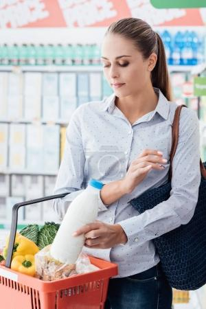 Woman doing grocery shopping at the supermarket, she is putting a bottle of milk into a shopping basket