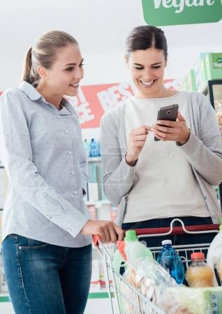 Girls shopping together at the supermarket and searching products using a smartphone